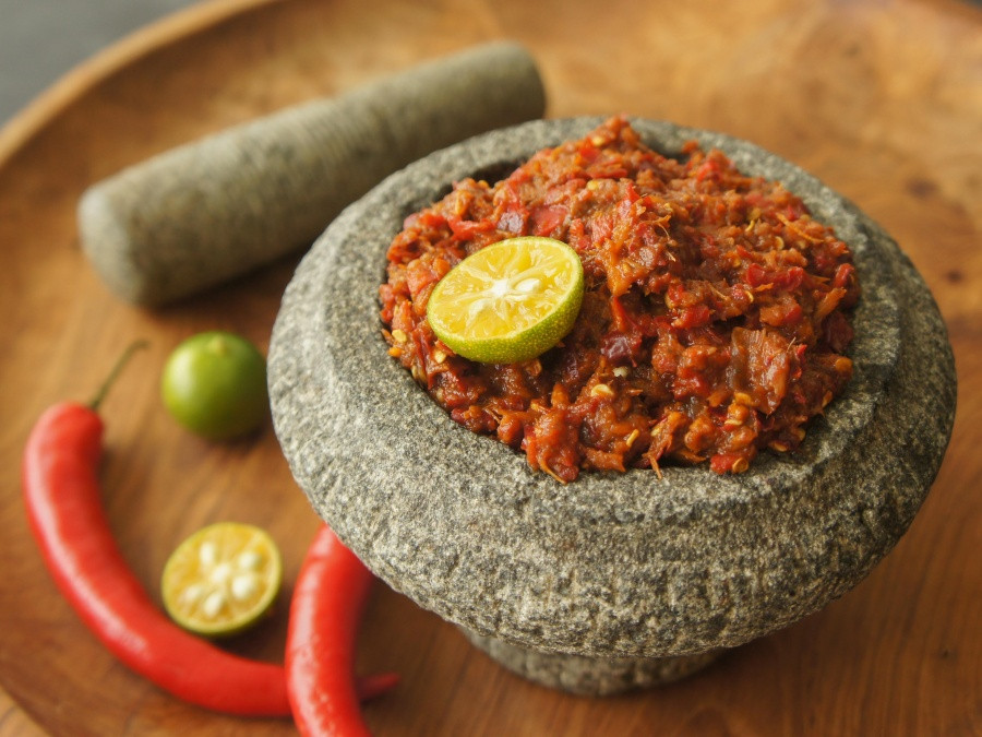 Vegan sambal belacan in a pestle, with a mortar, several chillies and cut limes on a wooden background.